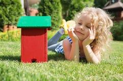 Little blonde girl lying on the grass Stock Photo