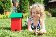 Little blonde girl lying on grass. Little blonde girl  lying on the grass with house toy Stock Photo