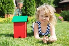 Little blonde girl lying on grass Stock Photo