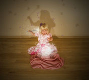 Little blonde girl and the magic spell. Little blonde girl casting a magic spell with a crystal ball, magic wand in her hands and butterflies flying around stock images