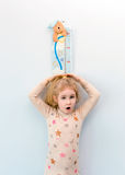 Little blonde girl measuring height against wall in room Royalty Free Stock Photography