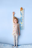 Little blonde girl measuring height against wall in room.  Royalty Free Stock Image