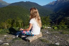 Little blonde girl meditating on top of mountain. Stock Image