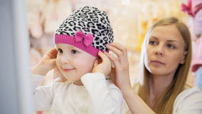 Little blonde girl with mommy doing shopping and buying hat in kids dress store Stock Photos
