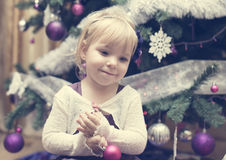 Little blonde girl near the Christmas tree Royalty Free Stock Photos