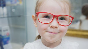Little blonde girl in ophthalmology clinic plays with pink glasses Stock Photography