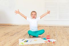Little blonde girl paintson big white paper sitting on the floor indoors royalty free stock photography