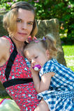 Little blonde girl with pigtails sleeping protected by the mom. Little blonde girl with pigtails sleeping on the lap of her mother on a spring meadow Stock Image