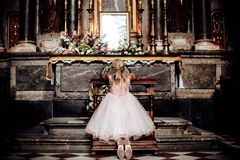 A LIttle blonde girl in a pink dress praying near the altar in the temple. View from behind.the girl kneels in church Royalty Free Stock Image