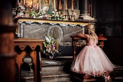 A LIttle blonde girl in a pink dress praying near the altar in the temple. View from behind.the girl kneels in church Stock Photos