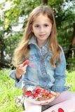 Little blonde girl with a plate of fresh strawberries in summertime Royalty Free Stock Image
