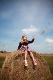 Little country blonde girl playing in the hay Stock Photos