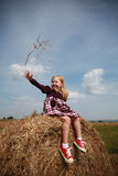 Little blonde girl playing in the hay Stock Images