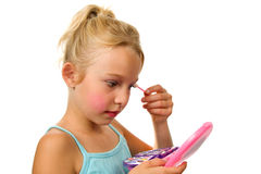 Little blonde girl is playing with make-up Stock Image