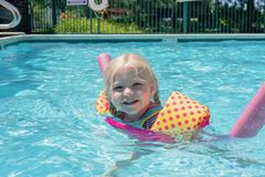 Little blonde girl playing at the pool on a summer day. Little blonde girl playing in the swimming pool on a hot summer day - childhood fun, summer vacation royalty free stock image