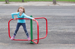 Little blonde girl playing on small merry go round. Happy little blonde girl playing on small merry go round on cloudy spring day Stock Photos