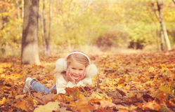 Little blonde girl portrait lying on autumn yellow maple leaves outstretched hands and smiling. Stock Photography