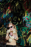 Little blonde girl posing next to wooden panel grafity Royalty Free Stock Photography