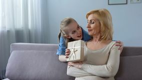 Little blonde girl presenting gift to grandmother and hugging her, relationship stock photo
