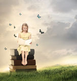 Little Blonde Girl Reading a Book. On Top of Books Royalty Free Stock Image