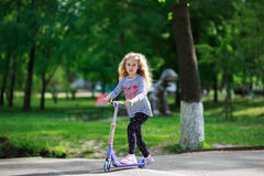 Little blonde girl ride the scooter in the park. Royalty Free Stock Photo