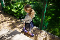 Little blonde girl ride the scooter in the park. Royalty Free Stock Image