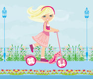 Little blonde girl riding a scooter Stock Photography
