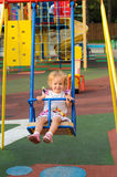 Little blonde girl riding on swing Royalty Free Stock Image
