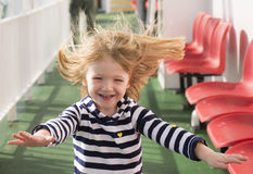 Little blonde girl running with windswept hair Stock Photo