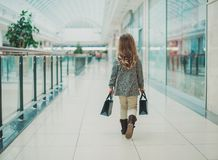 Little blonde girl is shopping at the Mall. Next to the black bags. Black Friday concept. Sale in stores royalty free stock images
