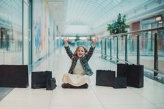 Little blonde girl is shopping at the Mall. She`s sitting. Next to the black bags. Black Friday concept. stock photos