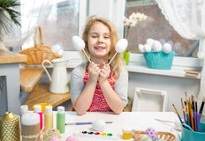 Little blonde girl showing eggs before coloring for Easter holiday at home Stock Photography