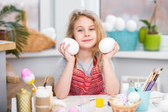 Little blonde girl showing eggs before coloring for Easter holiday at home Stock Images