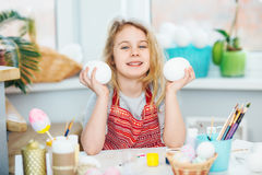Little blonde girl showing eggs before coloring for Easter holiday at home Royalty Free Stock Photography