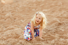 Little blonde girl sits on the coast of the bay and plays with s Royalty Free Stock Photo
