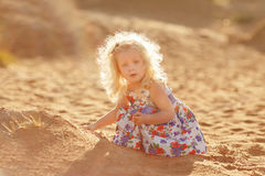 Little blonde girl sits on the coast of the bay and plays with s Royalty Free Stock Photography