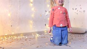 Little blonde girl sits on floor in living room and throws up bright confetti. Little blonde girl sits on floor in living room, child holds festive confetti in stock video footage
