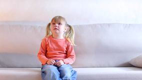 Little girl sitting on couch and crying, mother screaming at child for bad behavior.n. Little blonde girl sits on light sofa and cries, parents have punished for stock footage