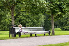 Little blonde girl sitting on the bench in the park. Little blonde girl sitting on the bench in the summer park looking to her side Stock Images