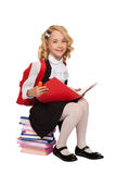 Little blonde girl sitting on the books holding textbook. With red bag pack over white background Royalty Free Stock Photo
