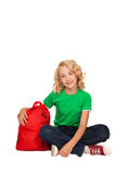 Little blonde girl sitting on the floor near books and bag Royalty Free Stock Images