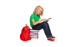 Little blonde girl sitting on the floor near books and bag. Over white background Stock Photo