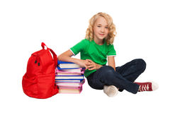 Little blonde girl sitting on the floor near books and bag Royalty Free Stock Photography