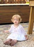 Little blonde girl sitting on gravel Royalty Free Stock Photos