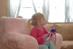 Little girl holding a princess wand and watching TV. Little blonde girl sitting in a pink plush chair holding a princess wand and watching TV Royalty Free Stock Photos