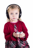 Little blonde girl smiling listening to music on Stock Photography