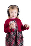 Little blonde girl smiling listening to music on Royalty Free Stock Photos