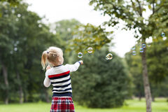 Little blonde girl with soap bubbles in green summer park. Little blonde girl playing with soap bubbles in green summer park Stock Image