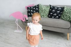 Little blonde girl standing near a couch in white room. Small girl and pink flamingo indoors.  royalty free stock image