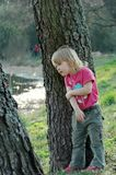 Little blonde girl. Blonde girl standing near the tree. Lake is behind. Girl observe wildlife Royalty Free Stock Images